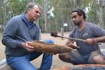 Gudathada Walker shows Richard Olive the traditional way to make tools.