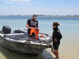 DPaW marine ranger Erin Clitheroe give a boater at Penguin Island a free rubbish bag